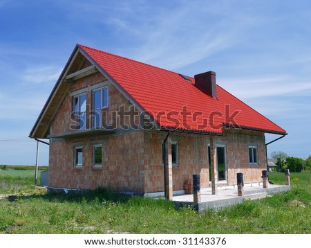 Unfinished single-family brick house covered by red sheet metal roof