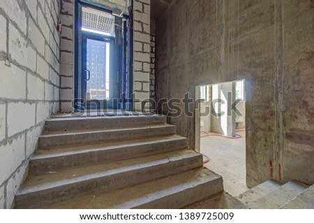 unfinished staircase to basement. Stairs architecture unfinished at basement. Cement concrete staircase on construction site. Empty and Bare Building Interior with Materials and Structure Exposed #1389725009