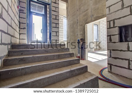 unfinished staircase to basement. Stairs architecture unfinished at basement. Cement concrete staircase on construction site. Empty and Bare Building Interior with Materials and Structure Exposed #1389725012