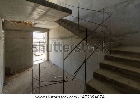 unfinished staircase to basement. Stairs architecture unfinished at basement. Cement concrete staircase on construction site. Empty and Bare Building Interior with Materials and Structure Exposed #1472394074