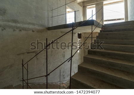 unfinished staircase to basement. Stairs architecture unfinished at basement. Cement concrete staircase on construction site. Empty and Bare Building Interior with Materials and Structure Exposed #1472394077