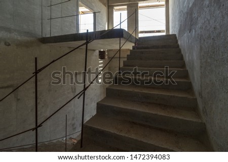 unfinished staircase to basement. Stairs architecture unfinished at basement. Cement concrete staircase on construction site. Empty and Bare Building Interior with Materials and Structure Exposed #1472394083