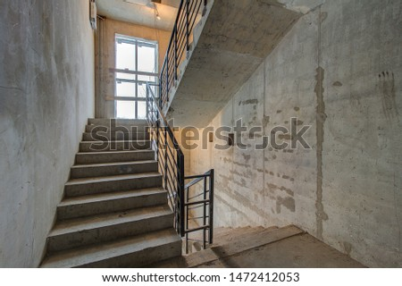 unfinished staircase to basement. Stairs architecture unfinished at basement. Cement concrete staircase on construction site. Building with Materials and Structure Exposed. entrance to house #1472412053
