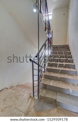 unfinished staircase to basement. Stairs architecture unfinished at basement. Cement concrete staircase on construction site. Building with Materials and Structure Exposed. entrance to house #1529509178