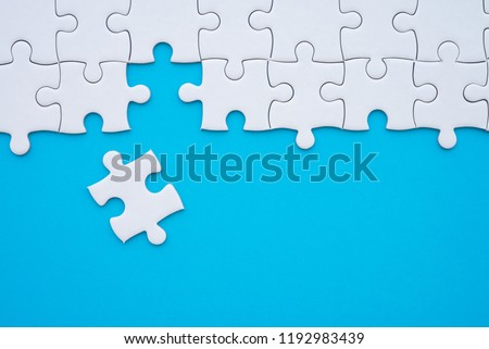 Unfinished white jigsaw puzzle on blue background with copy space. Business strategy teamwork and problem solving concept. Teamwork is collaborative effort of team to achieve goal or to complete task.