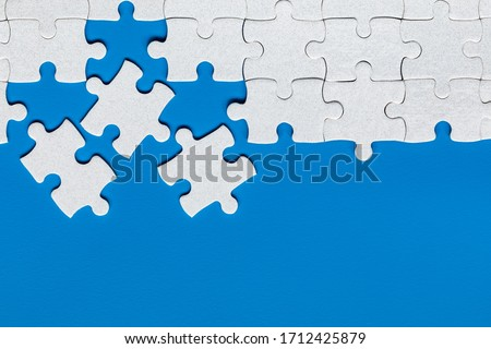 Unfinished white jigsaw puzzle pieces. Fill in pieces of the jigsaw puzzle. Complete the jigsaw puzzle with the missing pieces. Fragment of a folded white jigsaw puzzle.