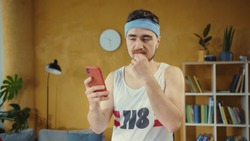 Unfit young man engaged in sports, using a smartphone, clicking on fitness app looking satisfied working out at home training.