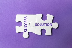 Unfitting white puzzle pieces with words SUCCESS and SOLUTION on purple background, top view