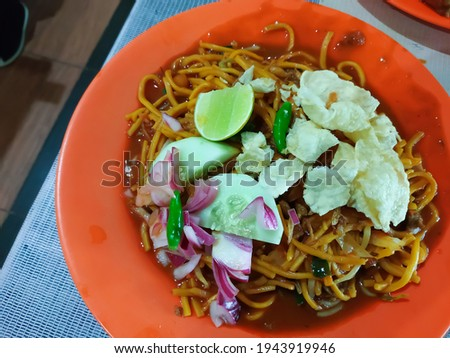 Unfocus picture of a plate of 'mie Aceh Medan'One of the favorite street food in Medan city. Mie Aceh consists of yellow noodles, pickled onions,cabbage,small pieces of beef and chips with spacy sauce Zdjęcia stock ©