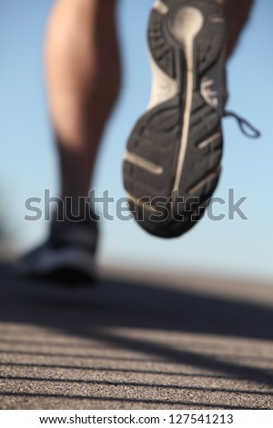 Unfocused man shoes running on the asphalt with the sky in the background