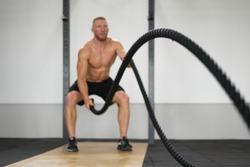 Unfocused unrecognizable man gym battle rope stamina training Athlete guy fitness exercising endurance indoor workout. Handsome caucasian sportive guy doing exercise functional training fitness.