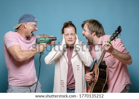 Unfortunate woman covered ears so as not to hear one neighbor playing the guitar, and the other working with a power drill. Stress. Photo stock ©