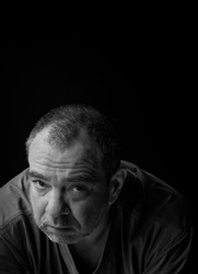 Unhappy adult man looking sullenly, black and white portrait