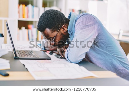 Unhappy african american male student concentrated on problem solution with project sitting at desktop, dark skinned workaholic feeling tired dozing at work on deadline via laptop computer in office