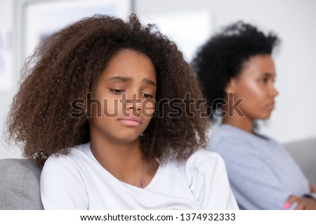 Unhappy African American teen girl having problem with strict mother, upset stubborn mum and unhappy teen girl child ignoring to each other, not talking after quarrel, family generation conflict