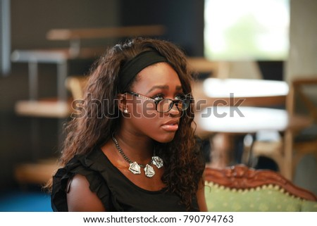 Unhappy African-American woman in stylish glasses and elegant outfit standing on blurred background.  #790794763