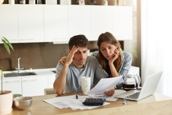 Unhappy American couple managing home accounts in kitchen, trying to save some money by cutting family expenses. Finances, bankruptcy, taxes, money, accounting and financial problems concept