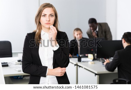 Unhappy and crying girl standing at modern open plan office on background with coworkers