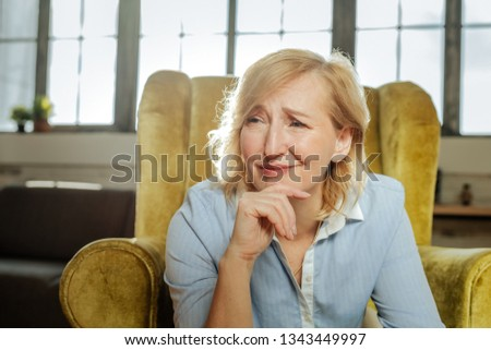 Unhappy and depressed. Unhappy misunderstood woman having weird face while sitting and leaning on her hand #1343449997