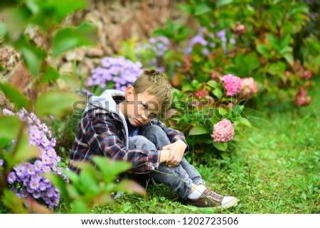 Unhappy and miserable. Little boy in deep sorrow. Little boy with sad look hide in garden. Little children little sorrow.