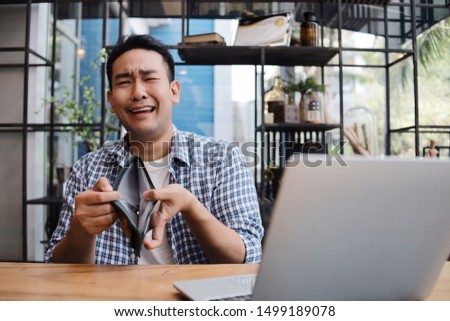 Unhappy Asian man with his empty wallet in coffee shop. Stock photo ©