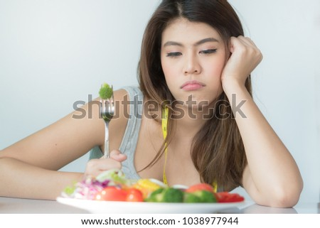 unhappy asian women is on dieting time looking at broccoli on the fork. girl do not want to eat vegetables and dislike taste of broccoli. #1038977944