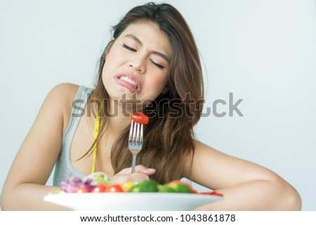 unhappy asian women is on dieting time looking at tomato on the fork. girl do not want to eat vegetables and dislike taste of tomato. #1043861878