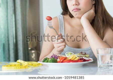 unhappy asian women is on dieting time looking at tomato on the fork. girl do not want to eat vegetables and dislike taste of vegetable. #1059481385