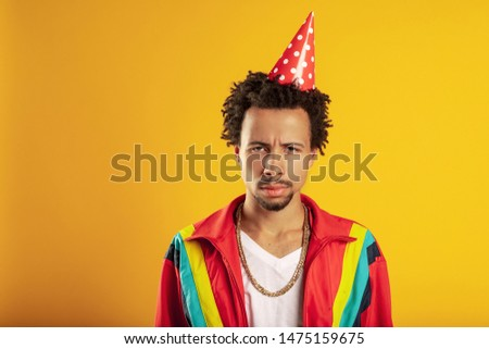 Unhappy birthday concept. Mournful sad frustrated man feels tired after preparing for celebration, wears paper hat, gold chain and colorful sport jacket wearing, upset someone ate his cookies #1475159675