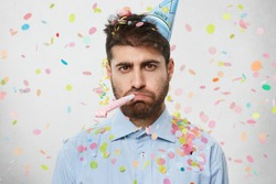 Unhappy birthday guy with stubble feeling sad and disappointed because nobody came to celebrate his anniversary, blowing party horn all alone, confetti flying around him. People and celebration