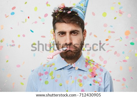 Unhappy birthday guy with stubble feeling sad and disappointed because nobody came to celebrate his anniversary, blowing party horn all alone, confetti flying around him. People and celebration Сток-фото ©