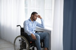 Unhappy black handicapped guy looking out window, feeling sad and desperate at home, copy space. African American man in wheelchair suffering from disability depression, indoors