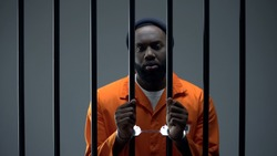 Unhappy black prisoner showing handcuffs, innocent male waiting for justice