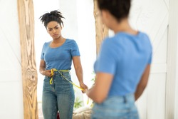 Unhappy Black Woman Measuring Waist With Tape Gaining Excess Weight Standing At Mirror Indoors. Selective Focus