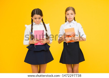 Unhappy bookworms. Unhappy little schoolchildren on yellow background. Adorable small girls with unhappy emotions holding books. Unhappy because of bad marks. #1472297738