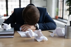 Unhappy businessman sit at desk in office feel depressed having no job inspiration make notes or drafts. Upset sad male employee or worker distressed with work, fall asleep or nap at workplace.