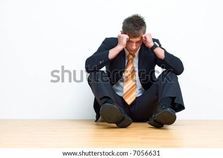 Unhappy businessman sitting on floor