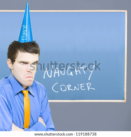 Unhappy Businessman Sulking In The Naughty Corner While Wearing A Dunce Hat In A Depiction Of A Bad Business Decision