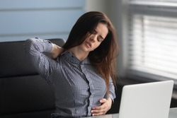 Unhappy businesswoman massaging neck, suffering from pain. Female employee massaging stiff neck muscles after sedentary computer work in incorrect posture or uncomfortable chair at workplace.