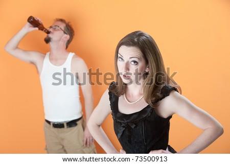 Unhappy Caucasian wife with alcoholic husband on orange background