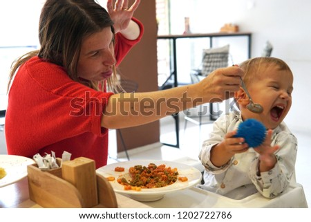 unhappy child refusing to eat at a restaurant with white background while mom is trying to deceive the toddler by tricks; anyway he does not want to eat