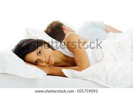 Unhappy couple lying in bed facing away from each other after and argument or fight.
