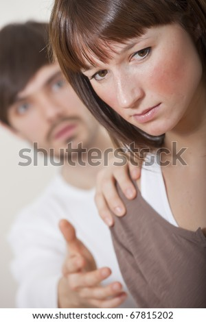 unhappy couple - man holding woman on her shoulder