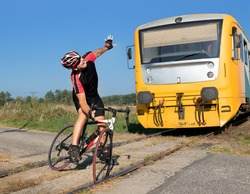 Unhappy cyclist has trouble on the railway crossing on Which the train is coming. The train goes to the cyclist stuck in the tracks. Accident on railway.