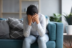 Unhappy depressed Indian woman holding head in hands, sitting alone on couch at home, stressed young female worried about bad relationship, break up, thinking about problems, feeling lonely