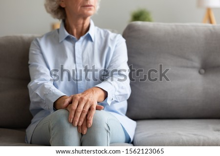 Unhappy depressed old senior woman sit alone on sofa with hands folded thinking of loneliness worried of disease or retirement problems feel anxiety grief suffer from arthritis concept, close up view