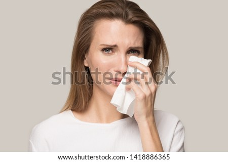 Unhappy depressed young woman crying, upset sad attractive female wiping tears, personal problem, divorce or break up with boyfriend, broken heart, seasonal allergy, isolated on studio background