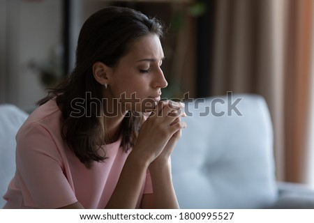 Unhappy distressed young Arabic indian woman sit on sofa at home thinking pondering, upset depressed arab mixed race female mourn yearn in living room, feel stressed with abortion miscarriage problems Stock photo ©