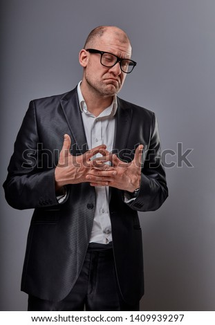e1eba407947f Unhappy doubt busuness man in black suit and glasses showing the palm  refusing sign on grey