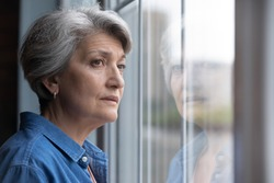 Unhappy elderly Caucasian 60s woman look in window distance mourning or yearning at home. Sad mature grey-haired female lost in thoughts feel lonely abandoned in retirement house. Solitude concept.